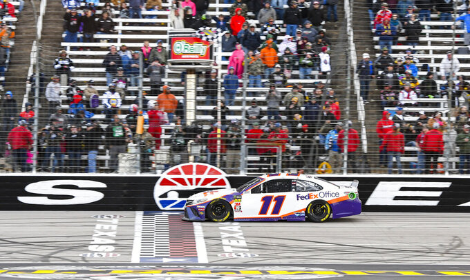 Driver Denny Hamlin takes the checkered flag to win a NASCAR Cup auto race at Texas Motor Speedway, Sunday, March 31, 2019, in Fort Worth, Texas. (AP Photo/Larry Papke)