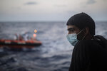 A migrant stands on on board the Spanish NGO Open Arms vessel with other people from different nationalities, including 14 minors and 4 women, on Wednesday Sept. 9, 2020, after being rescued last Tuesday night as they were trying to flee Libya on board a precarious wooden boat, in international waters, in the Central Mediterranean sea. (AP Photo/Santi Palacios)