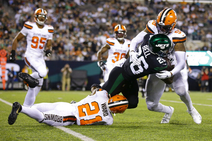 Cleveland Browns' Denzel Ward (21) and Christian Kirksey (58) tackle New York Jets' Le'Veon Bell (26) during the second half of an NFL football game Monday, Sept. 16, 2019, in East Rutherford, N.J. (AP Photo/Adam Hunger)