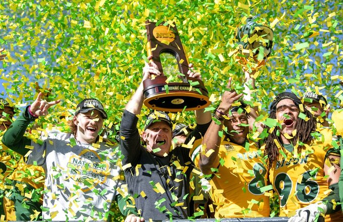 North Dakota State head coach Chris Klieman and his players hoist the trophy after beating Eastern Washington 38-24 in the FCS championship NCAA college football game, Saturday, Jan. 5, 2019, in Frisco, Texas. (AP Photo/Jeffrey McWhorter)