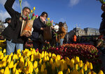 Scores of people pick free tulips on Dam Square in front of the Royal Palace in Amsterdam, Netherlands, Saturday, Jan. 18, 2020, on national tulip day which marks the opening of the 2020 tulip season. (AP Photo/Peter Dejong)