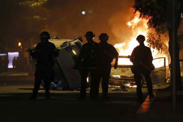 Police stand near a overturned vehicle and a fire as demonstrators protest the death of George Floyd, Sunday, May 31, 2020, near the White House in Washington. Floyd died after being restrained by Minneapolis police officers (AP Photo/Alex Brandon)