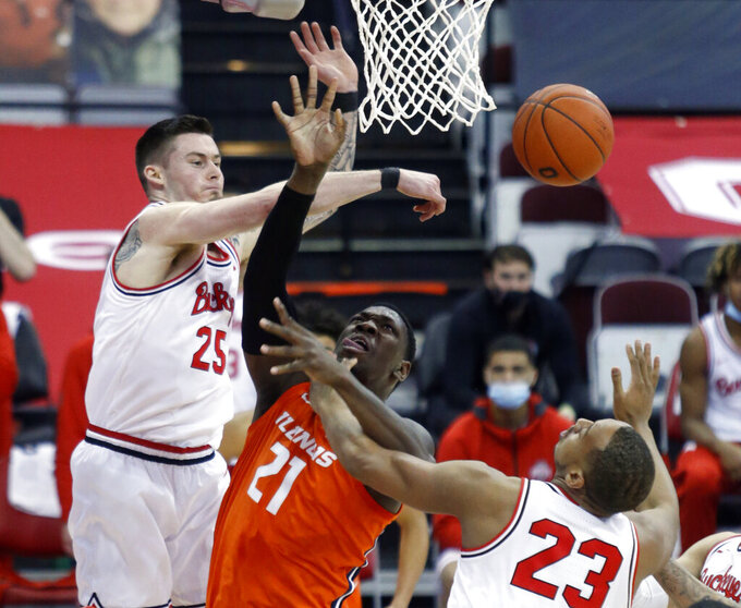 Ohio State forward Kyle Young, left, knocks the ball away from Illinois center Kofi Cockburn, center, as forward Zed Key defends during the first half of an NCAA college basketball game in Columbus, Ohio, Saturday, March 6, 2021. (AP Photo/Paul Vernon)