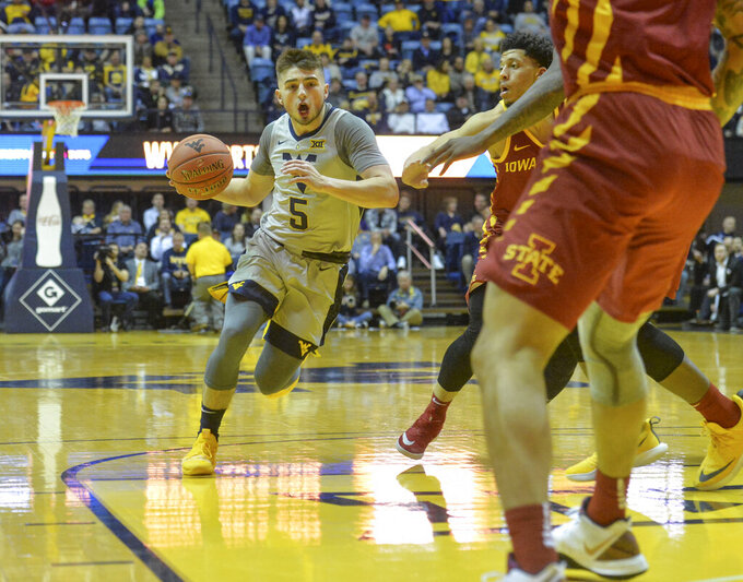 West Virginia guard Jordan McCabe (5) works the ball past Iowa State guard defenders during the first half of an NCAA college basketball game Wednesday, March 6, 2019, in Morgantown, W.Va. (William Wotring/The Dominion-Post via AP)