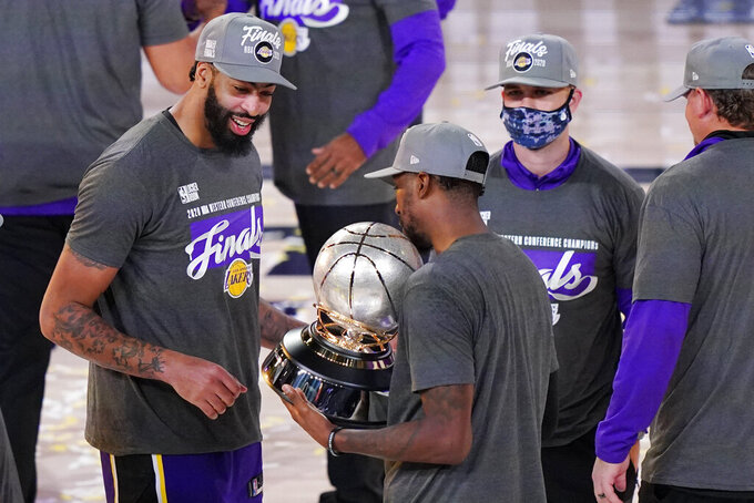 Los Angeles Lakers' Anthony Davis, left, looks at their trophy after beating the Denver Nuggets in an NBA conference final playoff basketball game Saturday, Sept. 26, 2020, in Lake Buena Vista, Fla. The Lakers won 117-107 to win the series 4-1. (AP Photo/Mark J. Terrill)