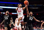 St. John's Nick Rutherford, center,  drives to the basket against Xavier's Naji Marshall (13) and KyKy Tandy (24) during an NCAA college basketball game in New York on Monday, Feb 17, 2020. (Steven Ryan/Newsday via AP)