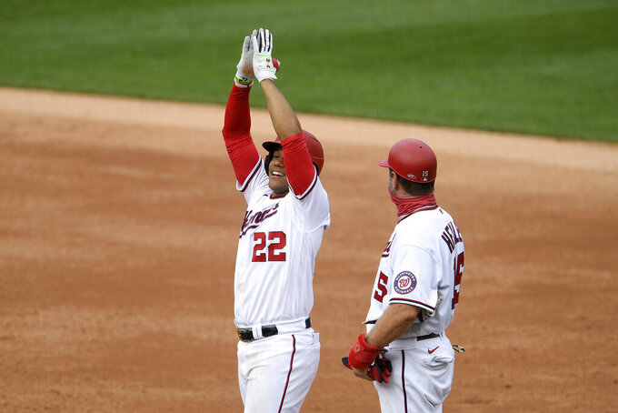 Washington Nationals' Juan Soto (22) reacts at first after his single during the second inning of a baseball game against the New York Mets, Sunday, Sept. 27, 2020, in Washington. Also seen is Nationals first base coach Bob Henley at right. The Nationals won 15-5. (AP Photo/Nick Wass)