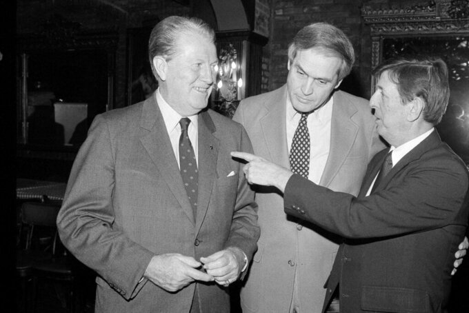 FILE - In this Dec. 28, 1982, file photo, Madison Square Garden Director of Intercollegiate Athletics Frank McGuire, left, jokes with Wake Forest coach Carl Tacy, center, and St. John's coach Lou Carnesecca during a basketball luncheon in New York. Former Wake Forest and Marshall basketball coach Carl Tacy has died at 87. Tacy's son, Carl Jr., told The Associated Press his father died early Thursday, April 2, 2020. (AP Photo/Mark Elias, File)