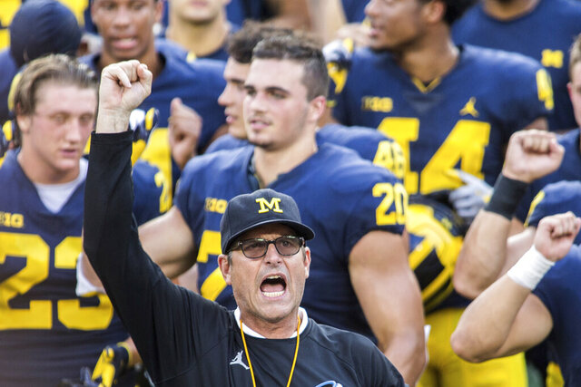 FILE  - In this Aug. 26, 2018, file photo, Michigan head coach Jim Harbaugh leads his players and fans in singing