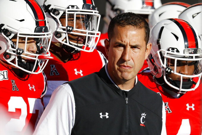 FILE - In this Saturday, Nov. 9, 2019, file photo, Cincinnati head coach Luke Fickell takes the field with his players before the first half of an NCAA college football game against Connecticut, in Cincinnati. Normally, in March, college football teams would be preparing for the upcoming season. Because of the new coronavirus pandemic, coaches are trying to figure out how to recreate some of what has been lost. Fickell said his goal is to try give his players a routine, including workout regimens they can do on their own without access to local gyms. They will also have online meetings with position groups and assistant coaches. (AP Photo/John Minchillo, File)