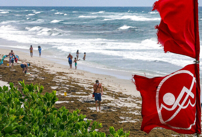 Red no swimming flags fly at Lantana, Fla., Municipal Beach, Fla., as Hurricane Isaias approaches the Florida coast Saturday, Aug.  1, 2020.  Isaias snapped trees and knocked out power as it blew through the Bahamas on Saturday and churned toward the Florida coast, where it is threatening to complicate efforts to contain the coronavirus in a hot spot.(Damon Higgins/The Palm Beach Post via AP)