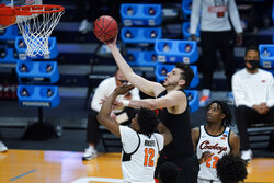 Oregon State center Roman Silva (12) shoots over Oklahoma State forward Matthew-Alexander Moncrieffe (12) during the first half of a men's college basketball game in the second round of the NCAA tournament at Hinkle Fieldhouse in Indianapolis, Sunday, March 21, 2021. (AP Photo/Paul Sancya)