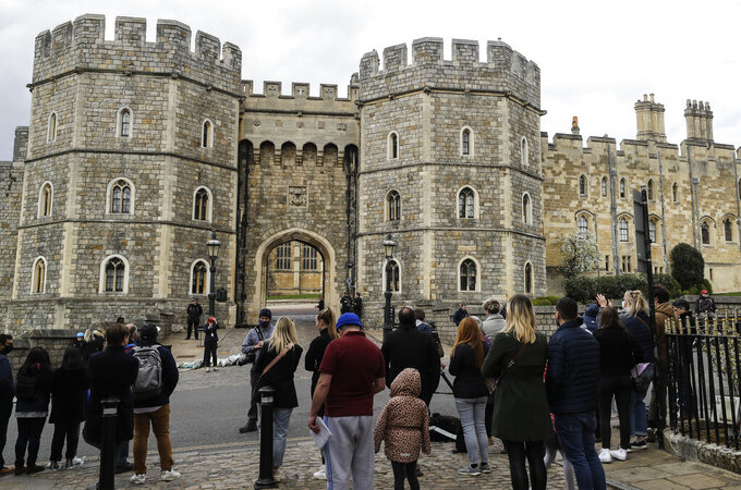 People gather outside Windsor Castle in Windsor, England after the announcement regarding the death of Britain's Prince Philip, Friday, April 9, 2021. Buckingham Palace officials say Prince Philip, the husband of Queen Elizabeth II, has died. He was 99. Philip spent a month in hospital earlier this year before being released on March 16 to return to Windsor Castle. (AP Photo/Kirsty Wigglesworth)