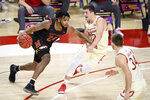 Maryland forward Donta Scott (24) drives against Wisconsin guards Trevor Anderson (12) and Brad Davison (34) during the first half of an NCAA college basketball game Wednesday, Jan. 27, 2021, in College Park, Md. (AP Photo/Nick Wass)