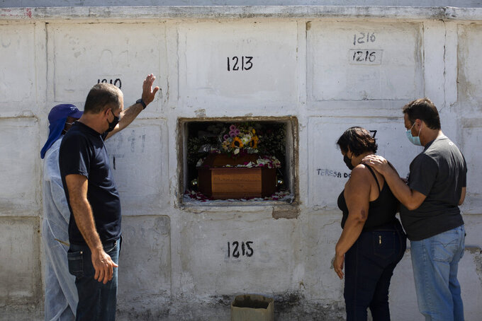 FILE - In this April 15, 2021, file photo, Carlos Alberto holds out his left arm during the burial service for his 41-year-old wife Aparecida de Freitas, who died from complications related to COVID-19, in the Inhauma cemetery, in Rio de Janeiro, Brazil. The global death toll from the coronavirus topped a staggering 3 million people Saturday, April 17, 2021, amid repeated setbacks in the worldwide vaccination campaign and a deepening crisis in places such as Brazil, India and France.  (AP Photo/Bruna Prado, File)