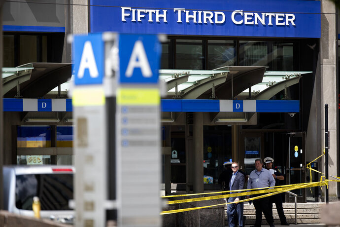 FILE - In this Sept. 6, 2018 file photo, police investigate outside Fifth Third Bank building on Fountain Square after a shooting with multiple fatalities in downtown Cincinnati. The two shooting victims who survived the gunman's attack are both back home. Whitney Austin was discharged from UC Medical Center on Tuesday, Sept. 11.  Brian Sarver was released Monday. (Albert Cesare/The Cincinnati Enquirer via AP, File)