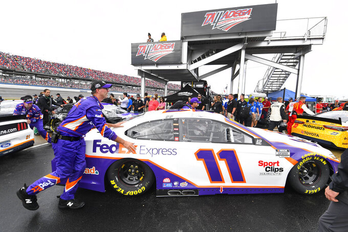 Team members push a car Denny Hamlin drives off pit row along with the rest of the field after a NASCAR Cup series auto race is postponed until Monday due to rain, Sunday, Oct. 3, 2021, in Talladega, Ala. (AP Photo/John Amis)