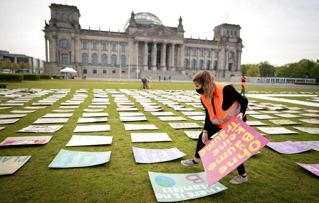 Luisa Neubauer of Fridays for Future movement lays out protest posters for climate protection in front the German parliament building the Reichstag in Berlin, Germany, Friday, April 24, 2020. Because of the continuing spread of the coronavirus, the climate strike will be digitally distributed on the Internet. (Kay Nietfeld/dpa via AP)
