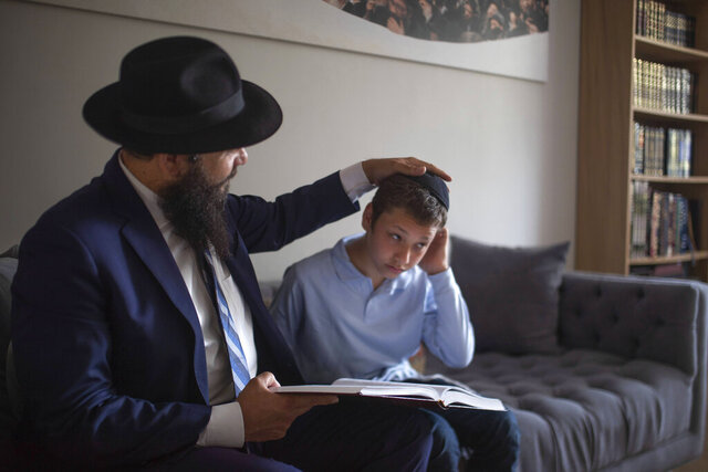 Chabad-Lubavitch Rabbi Levi Banon and his son Mendel, 12, read a religious text at their home library in Casablanca, Morocco, Thursday, May 28, 2020. (AP Photo/Mosa'ab Elshamy)