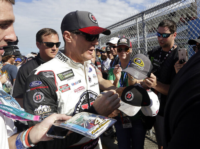 Kevin Harvick signs autographs before the NASCAR Series Championship auto race at the Homestead-Miami Speedway, Sunday, Nov. 18, 2018, in Homestead, Fla. (AP Photo/Lynne Sladky)