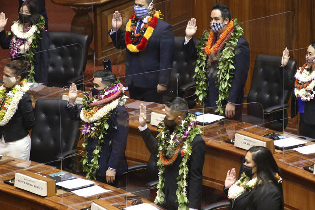 Members of the state House are sworn in Honolulu on Wednesday, Jan. 20, 2021. Lawmakers opened a new legislative session in the middle of a pandemic while wearing face masks and sitting next to clear plastic shields separating their seats. (AP Photo/Audrey McAvoy)