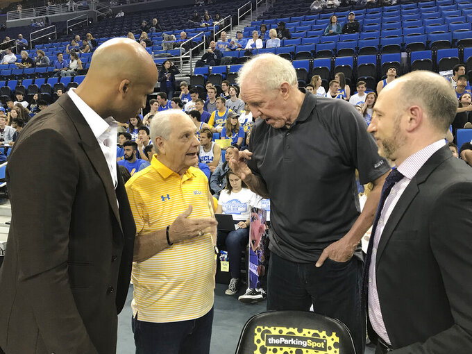 In this Feb. 29, 2020, photo provided by UCLA Athletics, Hep Cronin, second from left, talks with Richard Jefferson, left, and Bill Walton second from right, and Dave Pasch courtside at Pauley Pavilion in Los Angeles. Jefferson, Pasch and Walton were the ESPN crew for UCLA's game against Arizona. Hep had not seen his son, UCLA coach Mick Cronin, for over a year until the Bruins defeated Michigan State in the First Four. Hep has become an unlikely celebrity during the Bruins' run to the Final Four in his son's second season in Westwood. (UCLA Athletics via AP)