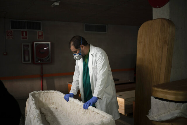 FILE - In this April 14, 2020, file photo, head mortician Jordi Fernandez prepares a coffin before placing the body of a COVID-19 victim in an underground parking garage turned into a morgue at the Collserola funeral home in Barcelona. The worldwide death toll from the coronavirus eclipsed 1 million, nine months into a crisis that has devastated the global economy, tested world leaders' resolve, pitted science against politics and forced multitudes to change the way they live, learn and work.  (AP Photo/Felipe Dana, File)