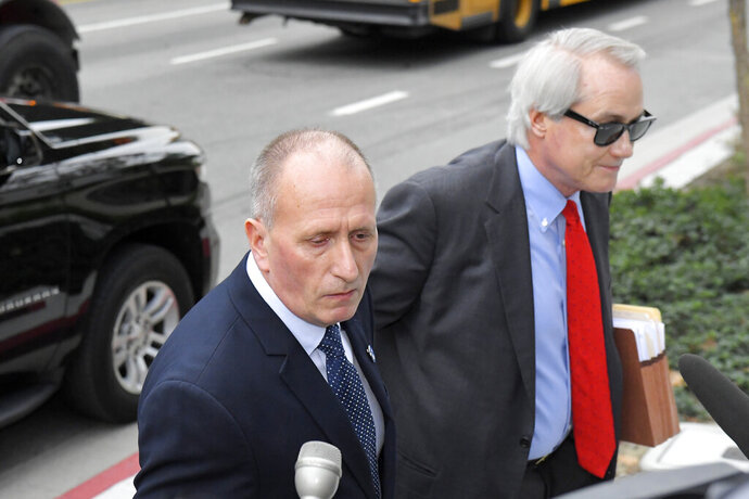 L. Lin Wood, right, attorney for plaintiff, British cave expert Vernon Unsworth, left, arrives for the trial against Tesla CEO Elon Musk at U.S. District Court Tuesday, Dec. 3, 2019, in Los Angeles. Musk is going on trial for his troublesome tweets in a case pitting the billionaire against a British diver he allegedly dubbed a pedophile. (AP Photo/Mark J. Terrill)