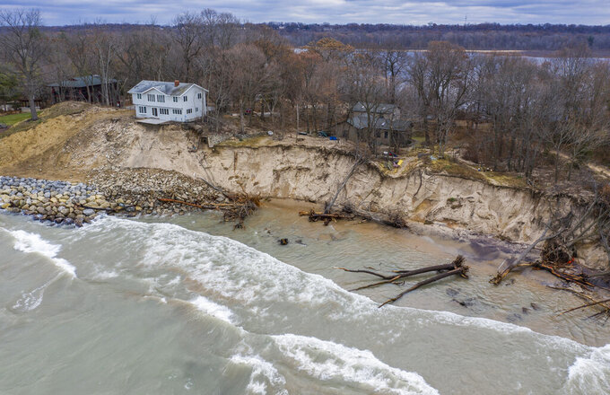 FILE - In this Dec. 4, 2019 file photo, erosion reaches a house along Lake Michigan's southwestern shoreline in Stevensville, Mich. A months-long spell of dry, mild weather is giving the Great Lakes a break after two years of high water that shattered records and heavily damaged shoreline roads and homes, officials said Monday May 10, 2021. (Robert Franklin/South Bend Tribune via AP. file)
