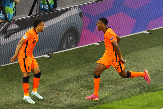 Netherlands' Denzel Dumfries, right, celebrates after scoring against Austria during the Euro 2020 soccer championship group C match between Netherland and Austria, at Johan Cruyff Arena in Amsterdam, Thursday, June 17, 2021. (Koen van Weel, Pool via AP)