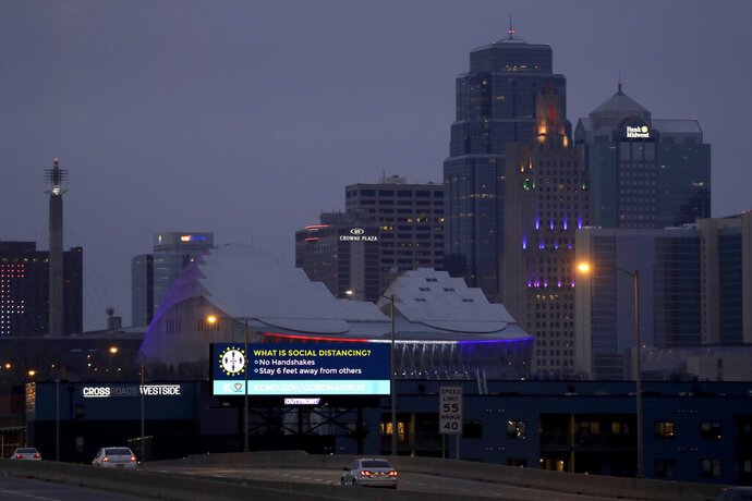 A sign about social distancing stands against the downtown skyline Tuesday, March 24, 2020 on the first day of a stay-at-home order in Kansas City, Mo. Kansas City and surrounding counties instituted a 30-day mandatory stay-at-home order in an effort to stem the spread of the coronavirus. (AP Photo/Charlie Riedel)