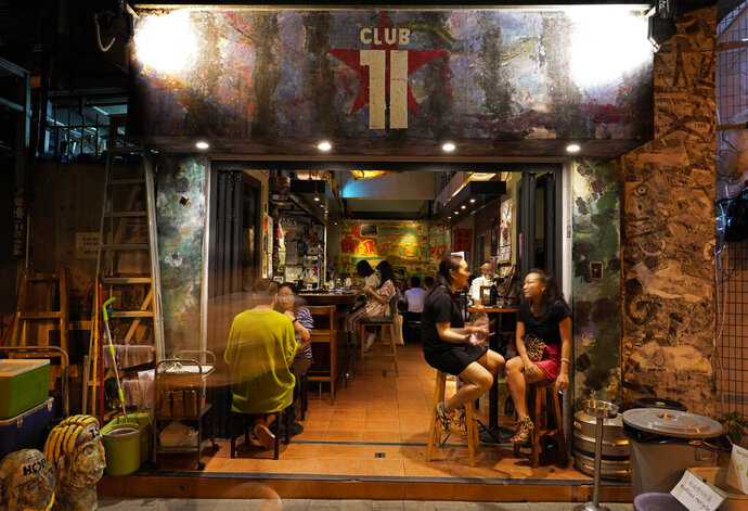 In this Oct. 7, 2020, photo, customers sit at Club 71 in Hong Kong. The bar known as a gathering place for pro-democracy activists and intellectuals is closing. (AP Photo/Vincent Yu)