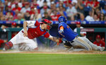 Philadelphia Phillies catcher J.T. Realmuto, left, tags out New York Mets' Jeff McNeil at home plate on a ball hit by Pete Alonso during the fourth inning of a baseball game, Tuesday, June 25, 2019, in Philadelphia. Alonso was safe at first on the play. (AP Photo/Matt Slocum)