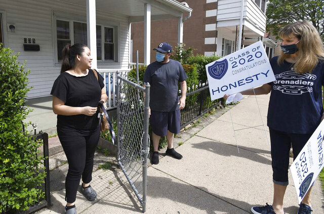 GAR High School teachers Tim Lavelle, left, and Kathy Genovese surprise GAR senior Honesty Lopez with her graduation yard sign, Wednesday, May 27, 2020, in Wilkes-Barre, Pa. GAR High School principals and teachers met earlier as a group to go out to student houses within the district to surprise the students with graduation yards signs. (Mark Moran/The Citizens' Voice via AP)