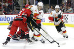 Calgary Flames' Matthew Tkachuk (19) and Johnny Gaudreau (13) chase the puck with Carolina Hurricanes center Lucas Wallmark (71), of Sweden, during the first period of an NHL hockey game in Raleigh, N.C., Tuesday, Oct. 29, 2019. (AP Photo/Gerry Broome)