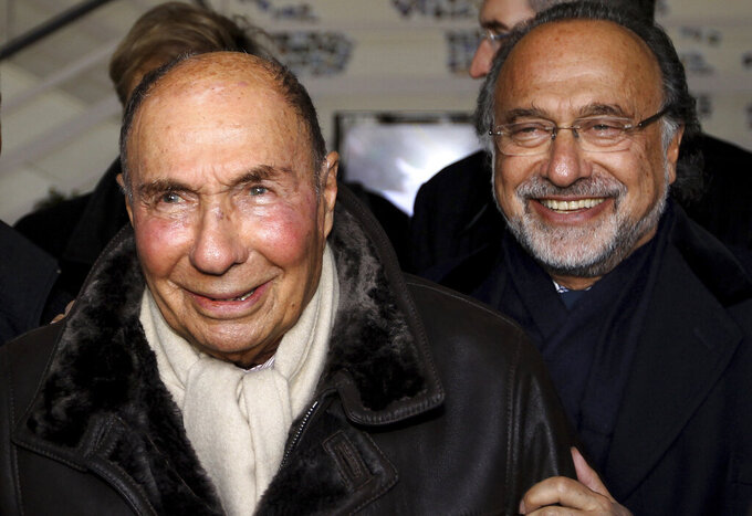 FILE - In this March 4, 2015 file photo, then Dassault Group Chairman and CEO Serge Dassault, left, and his son MP Olivier Dassault react as they visit the factory of French aircraft manufacturer Dassault Aviation in Merignac near Bordeaux, southwestern France. The French billionaire aviation industrialist Olivier Dassault who also served 19 years as a member of parliament died in a helicopter crash along with the pilot, authorities said. Olivier Dassault, 69, was heir to a powerful family business empire that made Falcon private jets and Rafale fighter planes and owned many other businesses including Le Figaro newspaper. (AP Photo/Bob Edme, File)