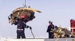 In this photo provided by the Russian Emergency Situations Ministry, emergency personnel load debris of an engine of the AN-148 plane crash on a truck in Stepanovskoye village, about 40 kilometers (25 miles) from the Domodedovo airport, Russia, Tuesday, Feb. 13, 2018. Emergency teams combed the snowy fields outside Moscow on Monday, searching for debris from a crashed Russian airliner and the remains of the 71 people aboard it who died. (Russian Ministry for Emergency Situations photo via AP)