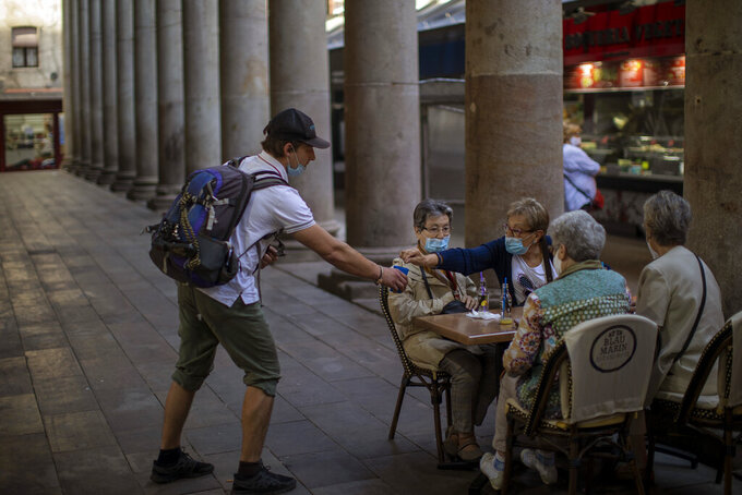 A woman gives alms to a beggar as they sit in a bar terrace during the coronavirus outbreak in Barcelona, Spain, Thursday, June 5, 2020. (AP Photo/Emilio Morenatti)