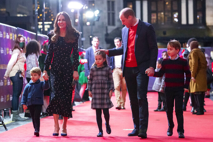 Britain's Prince William and Kate, Duchess of Cambridge talk to Dom Warren and family, the founder of Dom's Food Mission, as they attend a special pantomime performance at London's Palladium Theatre, Friday Dec. 11, 2020, hosted by The National Lottery, to thank key workers and their families for their efforts throughout the COVID-19 pandemic. (Aaron Chown/Pool via AP)