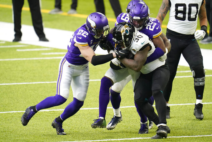 Jacksonville Jaguars running back James Robinson (30) is tackled by Minnesota Vikings safety Harrison Smith (22) and cornerback Kris Boyd (29) during the second half of an NFL football game, Sunday, Dec. 6, 2020, in Minneapolis. (AP Photo/Jim Mone)