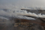 Plumes of smoke from fish processing rise above Bargny beach, some 35 kilometers (22 miles) east of Dakar, Senegal, Wednesday April 21, 2021. In Bargny and other coastal villages of Senegal, traditional fishing and processing of the catch is a livelihood and a pride. Methods have been passed down through generations. Women work as processors — drying, smoking, salting and fermenting the catch brought home by men (AP Photo/Leo Correa)