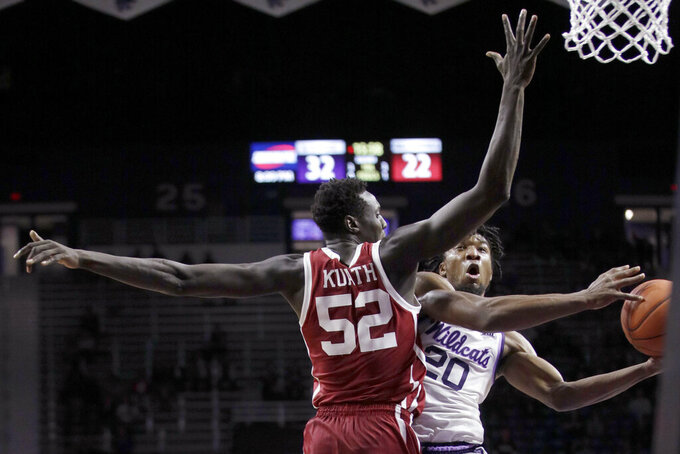 Kansas State forward Xavier Sneed (20) shoots while covered by Oklahoma forward Kur Kuath (52) during the second half of an NCAA college basketball game in Manhattan, Kan., Wednesday, Jan. 29, 2020. Kansas State won 61-53. (AP Photo/Orlin Wagner)