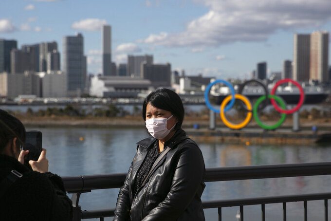 FILE - In this Jan. 29, 2020, file photo, a tourist wearing a mask poses for a photo with the Olympic rings in the background, at Tokyo's Odaiba district. Tokyo Olympic organizers repeated their message at the start of two days of meetings with the IOC: this summer's games will not be cancelled or postponed by the coronavirus spreading  neighboring China. (AP Photo/Jae C. Hong, File)