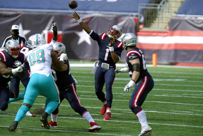 New England Patriots quarterback Cam Newton (1) passes under pressure from Miami Dolphins defensive tackle Raekwon Davis (98) in the first half of an NFL football game, Sunday, Sept. 13, 2020, in Foxborough, Mass. (AP Photo/Steven Senne)