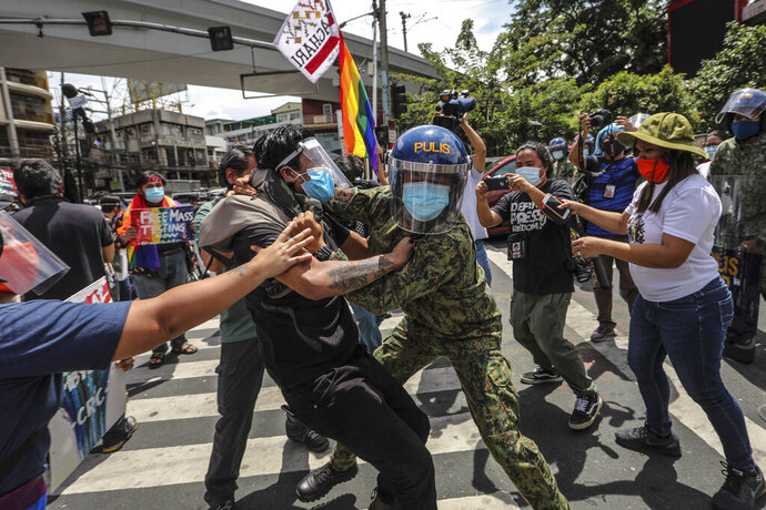 Police wearing face masks arrest protesters during a LGBTQ pride march in Manila, Philippines, Friday June 26, 2020. Philippine police  arrested 20 protesters who marked the Global Pride event with a march to demand government aid for poor workers and drivers displaced by the coronavirus lockdown. (AP Photo/Gerard Carreon)