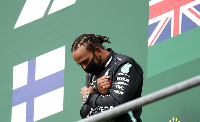 Mercedes driver Lewis Hamilton of Britain celebrates on the podium after winning the Formula One Grand Prix at the Spa-Francorchamps racetrack in Spa, Belgium, Sunday, Aug. 30, 2020. (Stephanie Lecocq, Pool via AP)