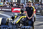Renault F1 Team driver Daniel Ricciardo sits on a tire of his car along Hollywood Boulevard in the Hollywood section of Los Angeles on Wednesday, Oct. 30, 2019. Ricciardo visited Los Angeles for the first time about five years ago after his cousin moved here, and the Renault driver quickly realized he felt right at home. He returned frequently, and he even bought a big house in the Hollywood hills last year. (AP Photo/Richard Vogel)