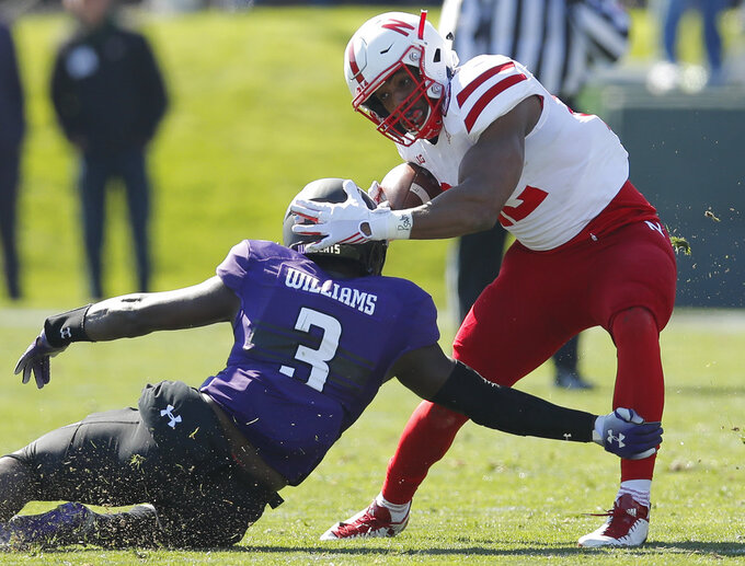 Nebraska's Devine Ozigbo, right, tries to break a tackle by Northwestern's Trae Williams during the first half of an NCAA college football game Saturday, Oct. 13, 2018, in Evanston, Ill.. (AP Photo/Jim Young)