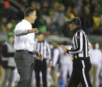 Oregon head football coach Mario Cristobal, left, talks to a referee during the second quarter against Arizona State in an NCAA college football game Saturday, Nov. 17, 2018, in Eugene, Ore. (AP Photo/Chris Pietsch)