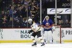 Boston Bruins fans cheer as Jake DeBrusk (74) skates past New York Islanders goaltender Semyon Varlamov (40) after scoring a goal during the second period of an NHL hockey game Saturday, Jan. 11, 2020, in New York. (AP Photo/Frank Franklin II)